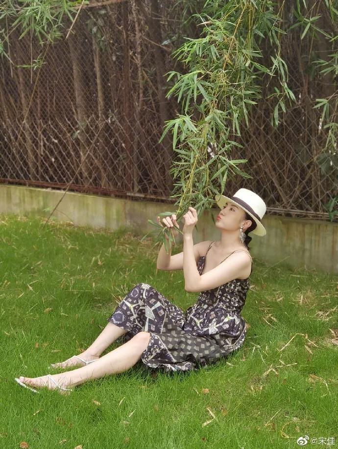 《【摩臣平台网站】宋佳草帽配吊带裙显风情 躺草地上悠闲身姿优美》